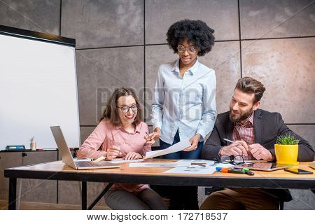Multi ethnic coworkers working together with documents and laptop at the workplace on the grey wall background