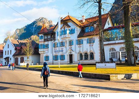Fussen, Germany - December 27, 2016: Beautiful painted traditional bavarian house and people near Neuschwanstein and german alps in Bavaria
