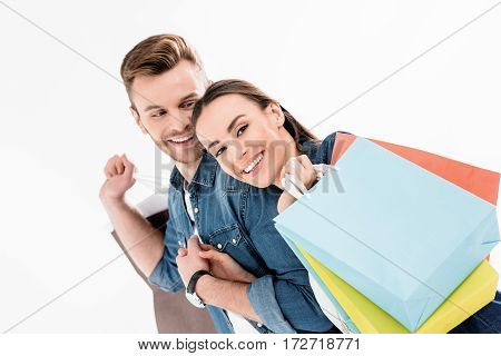 Portrait Of Smiling Man Looking At Woman With Shopping Bags On White