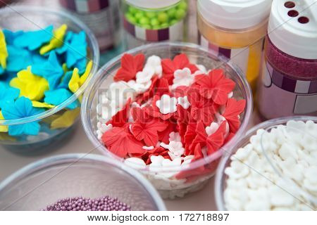 Ice cream treats and toppings sale. Rainbow sprinkles, stars, non pareil and glitter cupcake decorations, bright red and white. Closeup in plastic plates with spoons. Confectionery store