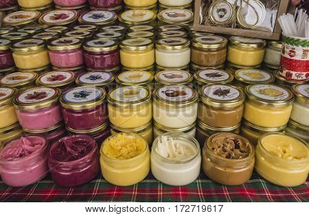 Honey with additives of herbs and berries. Jars with colored honey laid out in a row on the grocery market. Grocery honey background. An abundance of honey products.