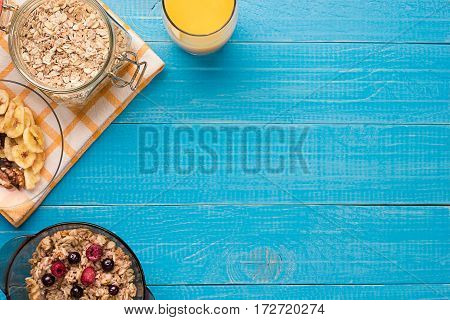 Breakfast with oatmeal and berries in bowl and orange juice in cup. Top view. Still life. Space for text.