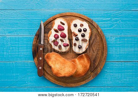 Butter sandwiches on healthy wholewheat bread topped with fresh raspberries, currants and raisins. Top view. Still life. Space for text.