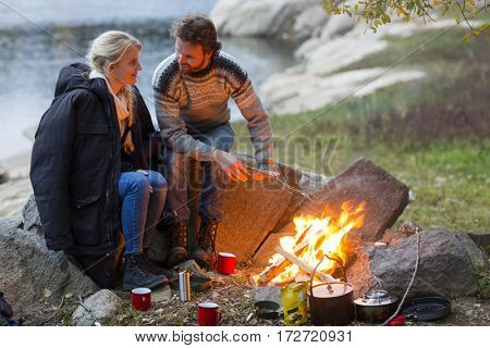Couple Looking At Each Other White Sitting By Campfire