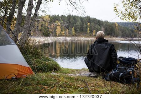 Male Backpacker Enjoying The View Of Lake At Campsite