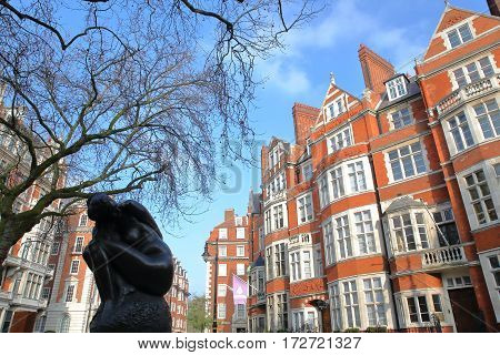 LONDON, UK - FEBRUARY 13, 2017: Red brick Victorian houses facades at Carlos Place in the borough of Westminster with a Statue (Silence Tadao Ando) in the foreground