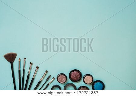 Colorful cosmetics on blue workplace with copy space. Cosmetics make up artist objects: eye shadows, tools for make-up.Top view. selective focus.