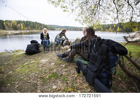 Friends Preparing For Lakeside Camping