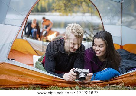 Couple Checking Pictures Into Camera While Lying In Tent