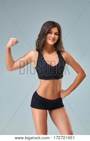the sports and beautiful young girl on a gray background. The lovely girl with a sports figure and a beautiful smile. The beautiful girl in a topic poses and shows press.
