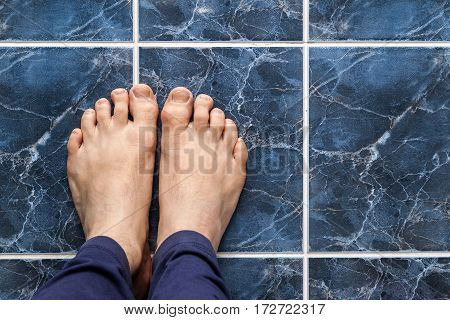 Young Man Crossing Feet On Square Tiles. Veins In Feet Visible.