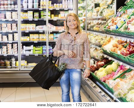 Woman Carrying Shopping Bag In Vegetable Department At Supermark