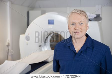 Professional Standing By MRI Machine In Hospital