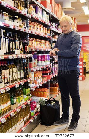 Man Using Smart Watch While Shopping In Supermarket
