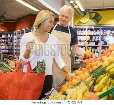 Salesman Choosing Fresh Oranges For Female Customer