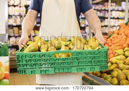 Salesman Carrying Pears In Crate At Grocery Store