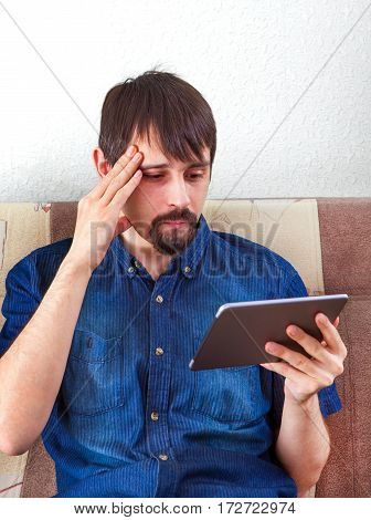 Troubled Man with Tablet Computer on the Sofa at the Home