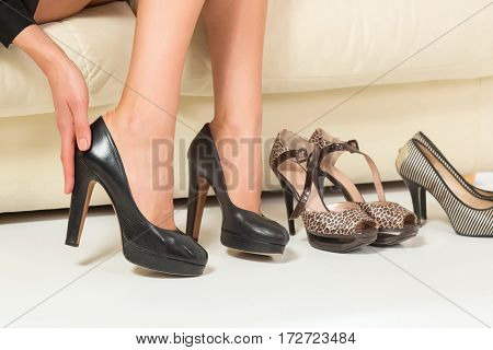 Woman choosing shoes or trouble with high heels. Sitting on the white sofa. Shopping.