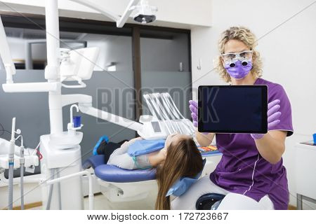 Dentist Showing Tablet Computer With Blank Screen By Patient