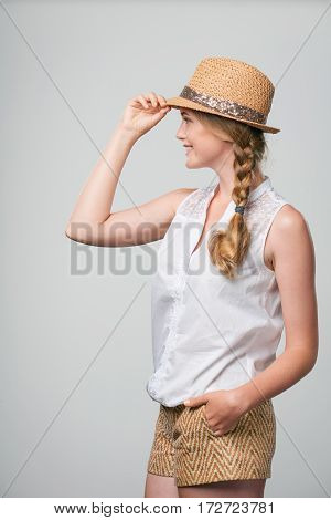 Side view of beautiful smiling woman summer woman looking forward and holding hat brim