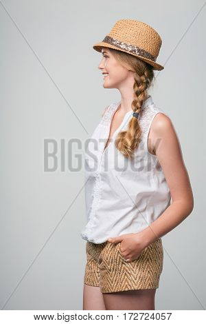 Side view of confident relaxed smiling woman looking forward with hands in pockets
