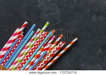 Colorful striped party cocktail straws on blackboard texture surface background with copy space. Bright plastic pipes