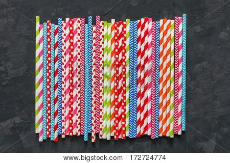 Colorful striped party cocktail straws row on blackboard surface background. Bright plastic pipes heap
