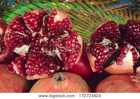 Juicy red pomegranate fruits in green leaves some with outer shell cracked. Ripe dissected pomegranates.