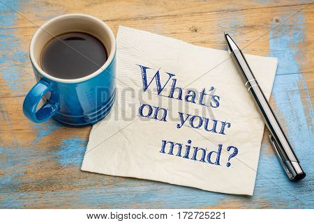What is on your mind question - handwriting on a napkin with a cup of espresso coffee
