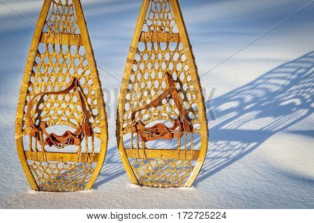 vintage wooden Huron snowshoes with leather binding in snow with shadow