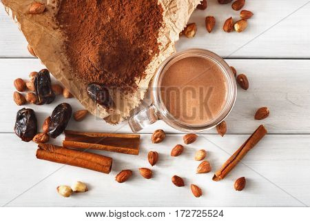 Detox cleanse drink background. Chocolate smoothie ingredients. Natural healthy juice in glass jar for diet or fasting day. Cocoa powder, nuts, cinnamon, date fruit mix on white wood, top view