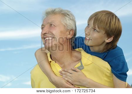 Cheerful young boy and his grandfather on a sky background