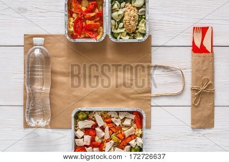Healthy food delivery. Take away of natural fitness dishes for diet. Daily meals in foil boxes on white wood. Vegetables, salmon, meat and salads. Top view, flat lay