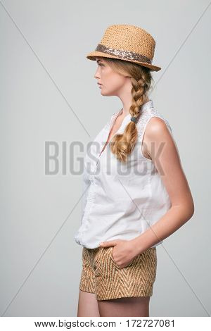 Side view of confident serious woman looking forward with hands in pockets