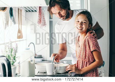 Dad with his 10 years old kid girl cooking in the kitchen, casual lifestyle photo series. Child making breakfast with parent together. Cozy homely scene.