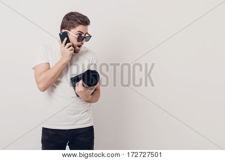 young professional photographer in a white shirt holds a heavy digital camera with a long lens and talking on the phone with a client