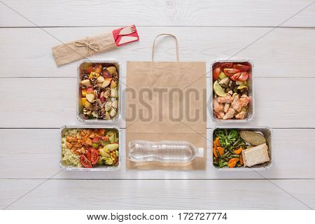 Healthy food delivery. Daily meals set top view in foil containers. Water, vegetable, fish, meat and fruits, low carb diet