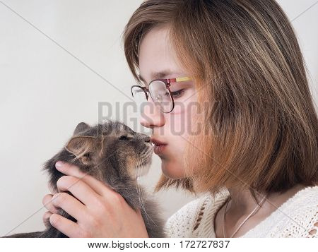 Girl and cat. Young girl with glasses is kissing gray cat