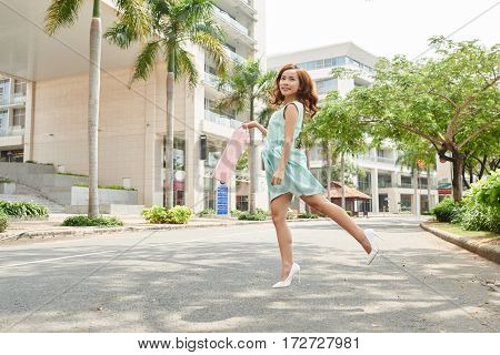 Attractive Asian woman in summer dress jumping in the street