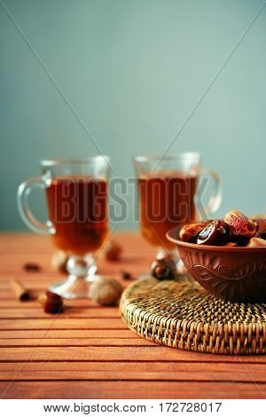 Bowl of dried dates and other spices on old wooden table with tea in glasses.
