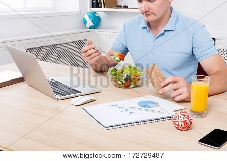 Man has healthy business lunch in modern office interior. Young handsome businessman at working place with vegetable salad in bowl, diet and eating right concept. Cropped