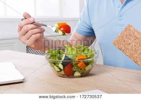 Unrecognizable man cropped image, healthy business lunch in modern office. Businessman in t-shirt at working place has vegetable salad in bowl, diet and eating right concept.