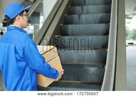 Courier with boxes and packages moving up the escalator