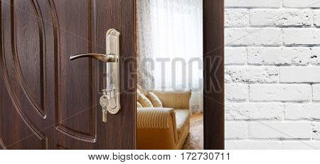 Half opened door handle closeup, entrance to a living room, sofa and window. Welcome, privacy concept. Door lock with keys, white brick wall, modern interior design.