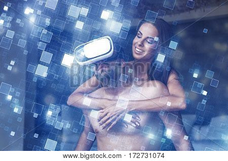 Young naked couple using VR headset virtual reality indoor glowing squares