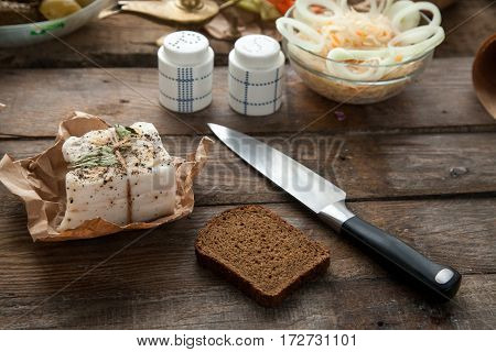 Ukrainian pork lard prepared for lunch with bread and pickle. Tasty high calorie meal for people who is not on diet.