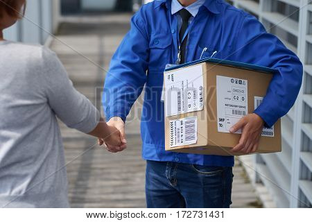 Delivery man with big box shaking hand of young woman