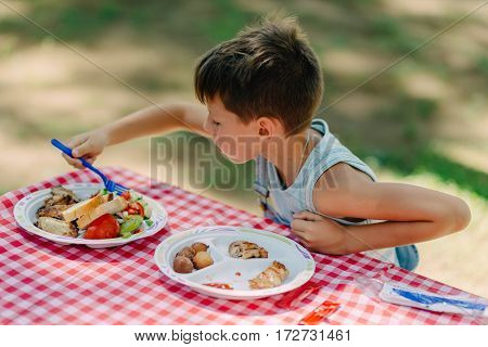 summer sunny day in nature at the table cute boy eats
