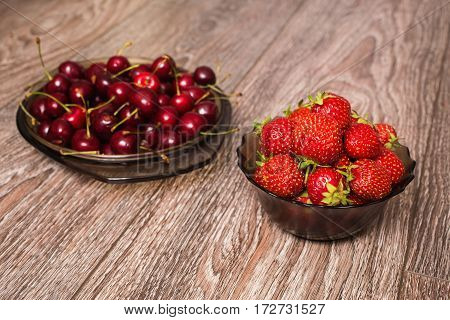 Berries in a bowl. Ripe juicy red cherry and a big red strawberry lying on the plate on a wooden background. Sweet summer berries.