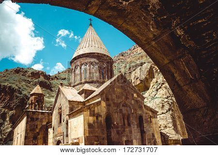 Entry through arch to cave monastery Geghard, Armenia. Armenian architecture. Pilgrimage place. Religion background. Travel concept. Church Astvatsatsin. Tourism industry